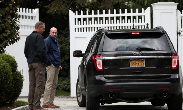 People stand outside the gatehouse of Bill and Hillary Clinton's house in Chappaqua, New York, U.S., October 24, 2018. REUTERS/Mike Segar