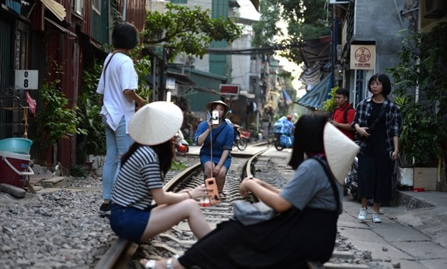 Tourists pose for a photo while sitting on a railway track passing through an old residential district in central Hanoi on Oct. 21, 2018. Nhac NGUYEN / AFP (AFP/Nhac Nguyen)