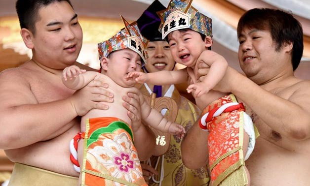 Sumo wrestlers hold up crying babies in front of a referee on May 14, 2017 - AFP