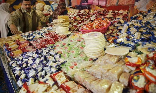 A vendor waits for customers to buy handmade sweets at a street market ahead of Mawlid al-Nabi, the birthday of Prophet Mohammad, in Old Cairo, Egypt, December 21, 2015. Picture taken December 21, 2015. REUTERS/Amr Abdallah Dalsh