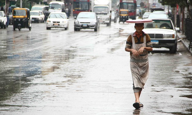 A child walking under the rain in Cairo - Ashraf Fawzy/Egypt Today