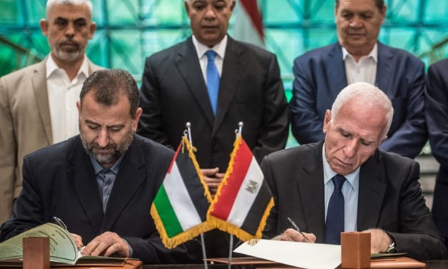 Fatah's Azam al-Ahmad (R)and Saleh al-Arouri of Hamas sign a reconciliation deal at the Egyptian intelligence services headquarters in Cairo on October 12, 2017.KHALED DESOUKI/AFP