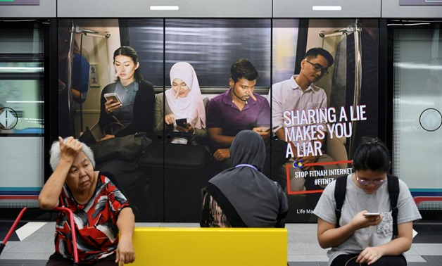 Commuters sit in front of an advertisement discouraging the dissemination of fake news, at a train station in Kuala Lumpur, Malaysia March 28, 2018. REUTERS/Stringer