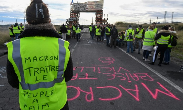 "Yellow vest protesters have blocked fuel depots like this one in Frontignan, southern France, where a woman's vest reads ""Macron, traitor, the people are hungry"""