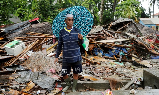 A man holding an umbrella walks through the debris of his damaged house after a tsunami in Sumur, Banten province, Indonesia December 26, 2018. Jorge Silva, Reuters