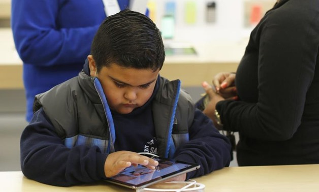 A child uses an iPad Air tablet at the Apple store in San Francisco, California November 1, 2013. REUTERS/Stephen Lam