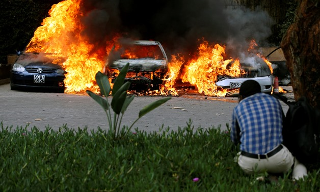 Cars are seen on fire at the scene of explosions and gunshots in Nairobi, Kenya January 15, 2019. REUTERS/Thomas Mukoya