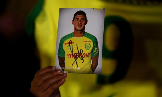 REFILE - ADDING RESTRICTIONS A fan holds a portrait of Emiliano Sala in Nantes' city center after news that newly-signed Cardiff City soccer player Emiliano Sala was missing after the light aircraft he was travelling in disappeared between France and Engl