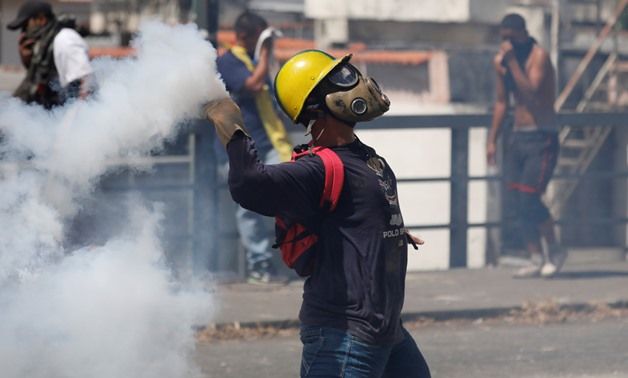 A demonstrator throws back a tear gas canister during a protest against Venezuelan President Nicolas Maduro's government in Caracas, Venezuela January 23, 2019. REUTERS/Manaure Quintero NO RESALES. NO ARCHIVES.