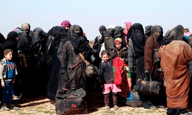 Civilians gather at a Syrian Democratic Forces outpost near the frontline village of Baghouz, on Jan. 26 ahead of being screened and registered by the SDF. (AFP)