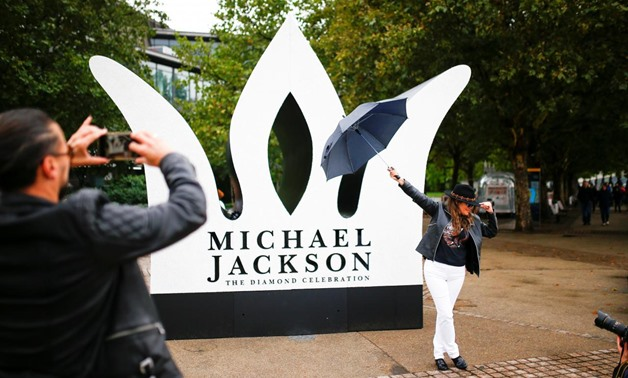 A fan has her photograph taken next to a Giant Crown installed to celebrate the diamond birthday of Michael Jackson, on the South Bank in London, Britain August 29, 2018. REUTERS/Henry Nicholls/File Photo