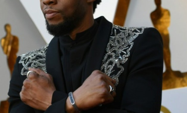"Actor Chadwick Boseman -- who plays the title role in ""Black Panther"" -- makes the Wakanda Forever arm gesture on the Oscars red carpet in March 2018 AFP/File"