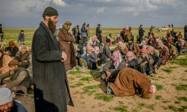 A man prays as men suspected of being Islamic State (IS) fighters wait to be searched by members of the Kurdish-led Syrian Democratic Forces (SDF) in Syria's northern Deir Ezzor province, on February 22, 2019 AFP/File