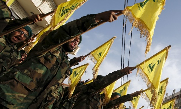 Lebanon's Hezbollah members carry Hezbollah flags. REUTERS/Ali Hashisho