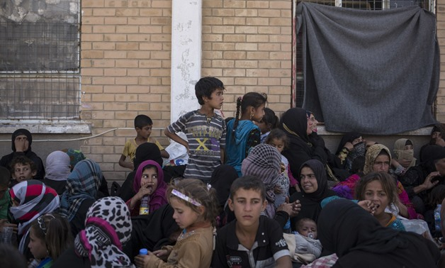 Women and children sit outside a Kurdish screening center to determine if they are associated with Daesh in this October 3, 2017 photo taken in Dibis, Iraq. (AP)