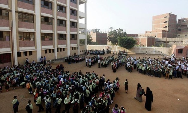 FILE - Students line up on the first day of their new school year at a government school in Giza – Reuters