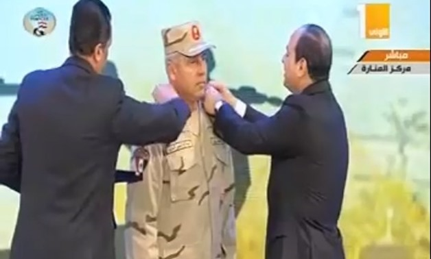 President Abdel Fatah al-Sisi changes shoulder marks for Chairman of the Armed Forces Engineering Authority Kamel Al-Wazir after he had promoted him to Lieutenant General from Major General during the celebration held in the occasion of 'Martyr Day' marki