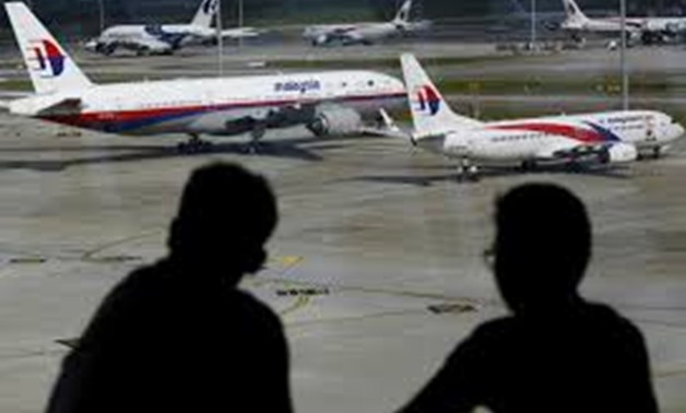 FILE PHOTO: Men watch Malaysia Airlines aircraft at Kuala Lumpur International Airport in Sepang, Malaysia, in this picture taken March 2, 2016. REUTERS/Olivia Harris/File Photo