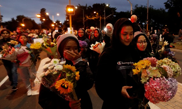 People reacts as they move the flowers after police removed a police line, outside Masjid Al Noor in Christchurch, New Zealand, March 16, 2019. REUTERS/Jorge Silva TPX IMAGES OF THE DAY