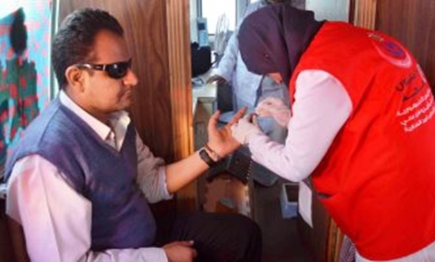"FILE - A doctor getting a blood sample of a citizen within ""100 Million Healthy Lives"" campaign targeting to screen Egyptians for Hepatitis C and provide free treatment"