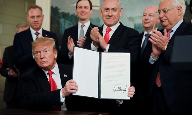 U.S. President Donald Trump holds a proclamation recognizing Israel's sovereignty over the Golan Heights as he is applauded by Israel's Prime Minister Benjamin Netanyahu and others during a ceremony to in the Diplomatic Reception Room at the White House i