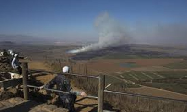 Druze men look at smoke rising on the Israeli-controlled side of the line dividing the Israeli-occupied Golan Heights from Syria following fighting near the Quneitra border crossing, August 27, 2014. REUTERS/Ronen Zvulun