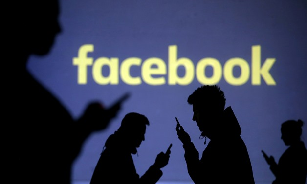 FILE PHOTO: Silhouettes of mobile users are seen next to a screen projection of Facebook logo in this picture illustration taken March 28, 2018. REUTERS/Dado Ruvic/Illustration