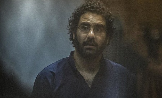 Egyptian activist and blogger Alaa Abdel Fattah looks on from behind the defendant's cage during his trial. (AFP)