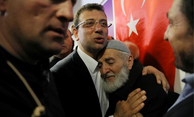 FILE PHOTO: Ekrem Imamoglu, main opposition Republican People's Party (CHP) candidate for mayor of Istanbul, embraces his supporter at his election campaign office in Istanbul, Turkey April 1, 2019. REUTERS/Huseyin Aldemir/File Photo