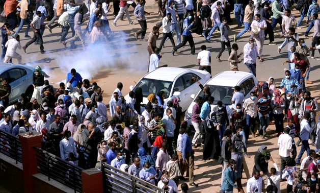 FILE PHOTO: Sudanese demonstrators run from teargas lobbed to disperse them as they march along the street during anti-government protests in Khartoum