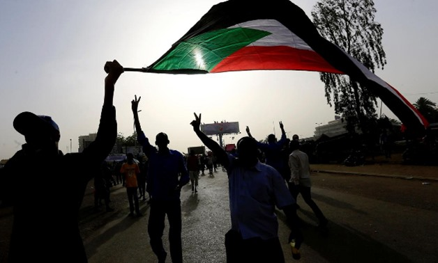 Sudanese demonstrators wave their national flag as they arrive for a protest rally demanding Sudanese President Omar Al-Bashir to step down outside the Defence Ministry in Khartoum, Sudan April 11, 2019. REUTERS/Stringer