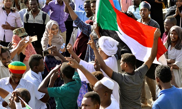Sudanese demonstrators celebrate after Defence Minister Awad Ibn Auf stepped down as head of the country's transitional ruling military council, as protesters demanded quicker political change, near the Defence Ministry in Khartoum, Sudan April 13, 2019.