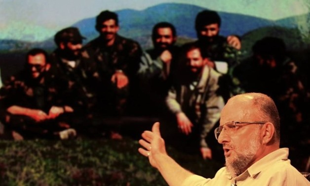 Iranian controversial conservative activist Saeed Ghasemi during an Interview with a photo in background showing him and his comrades during the Bosnian conflict in the early 1990s - Tasnim