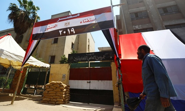 An Egyptian man walks in front of a school used as a polling station covered from outside by Egyptian flags, during the preparations for the upcoming referendum on constitutional amendments in Cairo, Egypt April 18, 2019. REUTERS/Amr Abdallah Dalsh