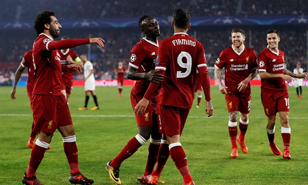 Liverpool players celebrate scoring a goal, Reuters