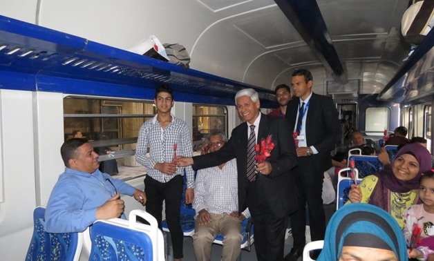 The Public Relations manager of the Egyptian National Railway and commuters pose for a photo at Cairo-Alexandria train after distributing candy and flowers to train commuters - Egypt Today/ Azoz Al-Dib