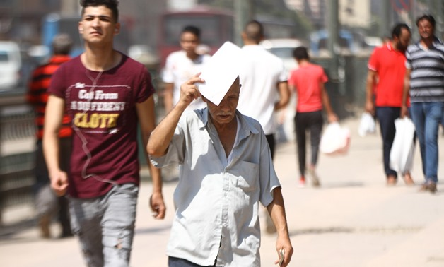 FILE- An Egyptian man covers his head with a paper to avoid the sun rays amid high temperature in Cairo- the photo was taken on August 3, 2018- Egypt Today/Mohamed Fawzy