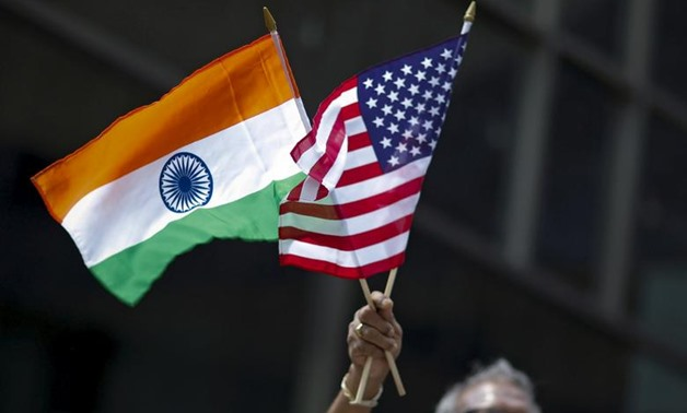FILE PHOTO: A man holds the flags of India and the U.S. while people take part in the 35th India Day Parade in New York August 16, 2015. REUTERS/Eduardo Munoz