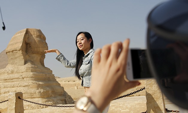 A Chinese tourist poses for a photo in front of the Sphinx at the Giza Pyramids on the outskirts of Cairo, Egypt, March 2, 2016 - REUTERS/Amr Abdallah Dalsh