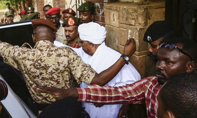 Sudan's ousted president Omar al-Bashir (C) is escorted into a vehicle as he returns to prison following his appearance before prosecutors over charges of corruption and illegal possession of foreign currency, in the capital Khartoum on June 16, 2019. Bas