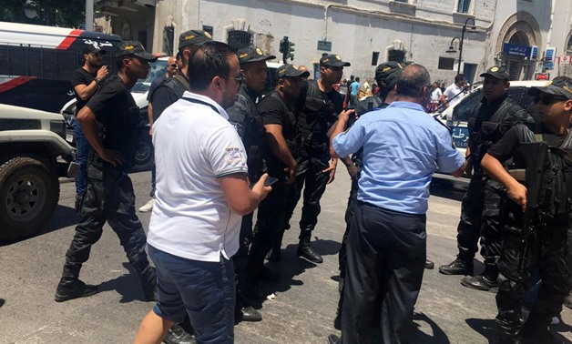 Police officers stand guard at the site of an explosion at Charles de Gaulle street in downtown Tunis