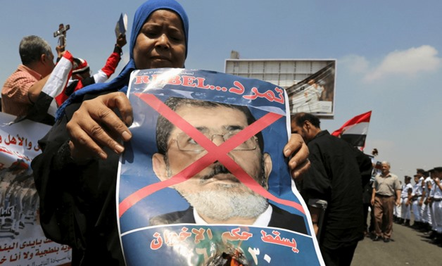 A woman burns a portrait of ousted President Mohamed Morsi at the funeral of Egyptian public prosecutor Hisham Barakat, on the second anniversary of the June 30 protests, in Cairo, Egypt, June 30, 2015.