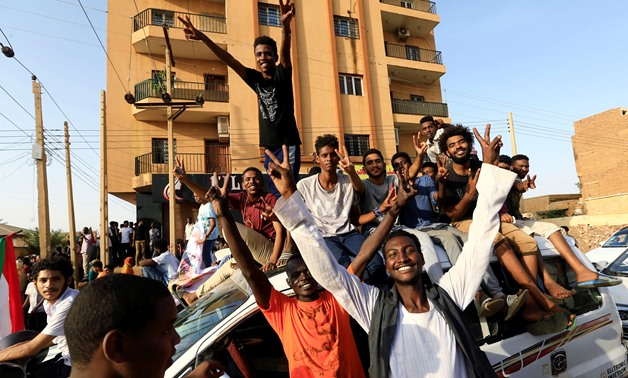 FILE- Sudanese people chant slogans as they celebrate, after Sudan's ruling military council and a coalition of opposition and protest groups reached an agreement to share power during a transition period leading to elections, along the streets of Khartou