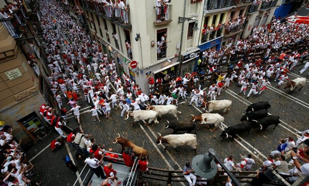 Revellers sprint in front of bulls and steers during the first running of the bulls at the San Fermin festival in Pamplona, Spain, July 7, 2019. REUTERS/Susana Vera