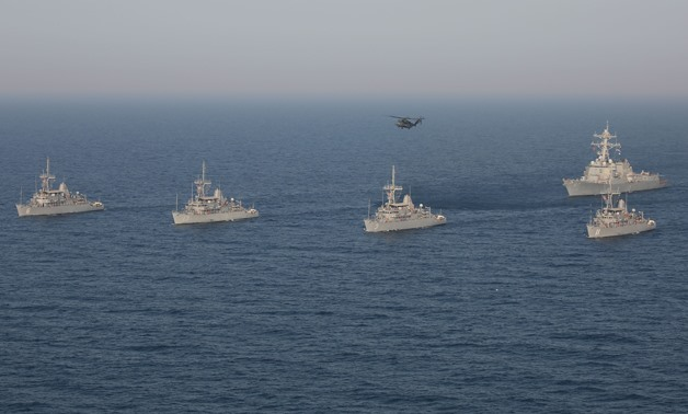 A formation of Avenger-class mine countermeasure ships USS Devastator (MCM 6), USS Gladiator (MCM 11), USS Sentry (MCM 3), USS Dextrous (MCM 13), the Arleigh Burke-class guided missile destroyer USS Mason (DDG 87) and an MH-53E Sea Dragon helicopter assig