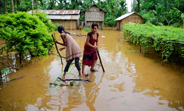 Girls row a makeshift raft past submerged houses at a flood-affected village in Karbi Anglong district, in the northeastern state of Assam, India, July 11, 2019. REUTERS/Anuwar Hazarika TPX IMAGES OF THE DAY
