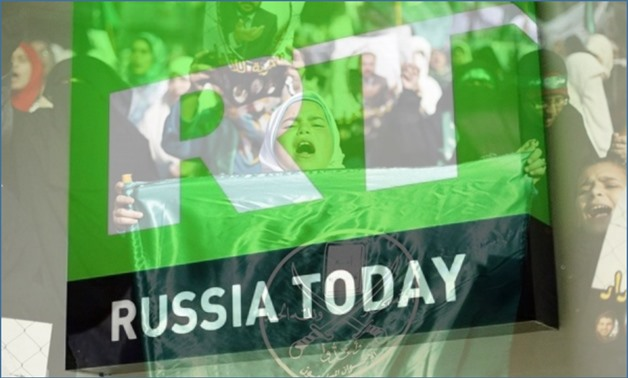 Compiled photo: A girl carries a flag of the Muslim Brotherhood in Amman – Reuters, and picture of Russia Today logo from an open source
