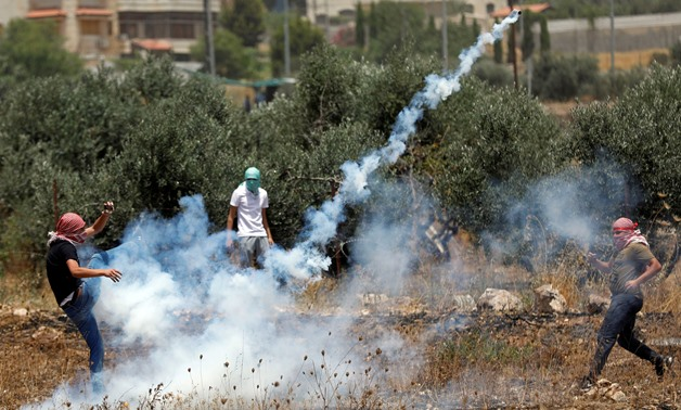 A Palestinian demonstrator kicks a tear gas canister fired by Israeli forces, in the Israeli-occupied West Bank July 17, 2019. REUTERS/Moha