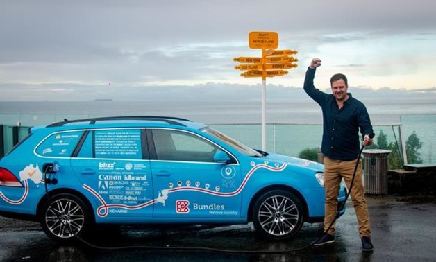 Dutchman Wiebe Wakker holds a charging cable as he poses with his electric vehicle, the Blue Bandit, after travelling 34 countries to reach Bluff, New Zealand's most southern tip, in this handout photo released July 19, 2019. Wiebe Wakker/Handout via REUT