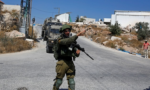An Israeli soldier gestures during a raid after the Israeli military said an Israeli soldier was found stabbed to death near a Jewish settlement, in Beit Fajjar in the Israeli-occupied West Bank August 8, 2019. REUTERS/Mussa Qawasma